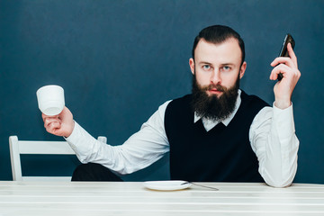 Businessman holding a coffee and looking at the camera .