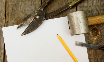 Paper with pencil and the vintage working tools on wooden
