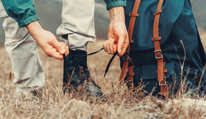 Hiker man tying shoelaces on nature