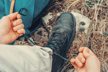 Traveler man tying shoelaces on nature