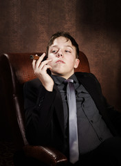 Young cigar smoker sitting in arm-chair