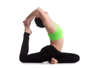 Beautiful sporty girl practices yoga one-legged King Pigeon Pose