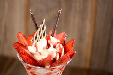 Erdbeer-Eisbecher auf Holzhintergrund