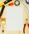 Paper for notes and set of working tools on wooden background.
