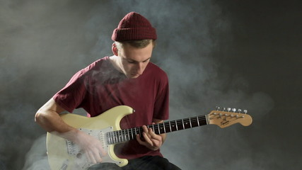 A talented musician playing guitar in a dark studio in smoke