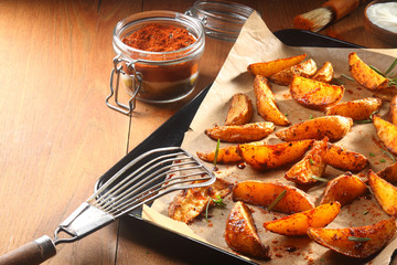 Hot Spicy Potato Wedges on Tray with Slotted Ladle