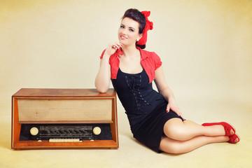 Pinup sitzt neben altem Radio