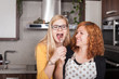 Excited girlfriends eating in the kitchen