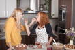 Girlfriends feeding each other in the kitchen