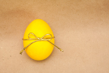yellow egg with bowknot on kraft background