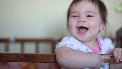 Little baby girl standing on the bed and laughing
