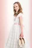 Cute Communion girl holding shoes.