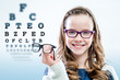 Girl holding glasses with test chart in background. - 79947582
