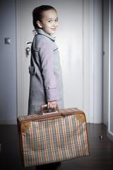 Niña sonriente con maleta vintage en la mano