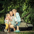 family on a background of an old vintage military tank