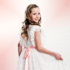 Studio portrait of cute girl in communion dress.