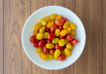 Red and yellow tomatoes in white bowl
