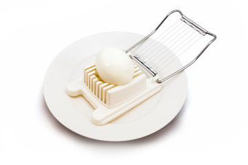 Boiled egg in an egg slicer isolated on white background