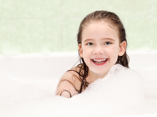 Smiling little girl washing in bath
