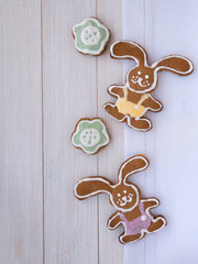 Easter Bunny and green flower cookies on the white wooden backgr