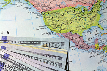 Money atop an old atlas