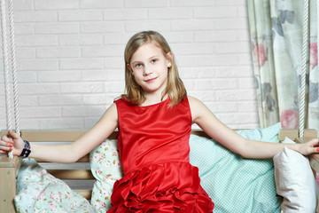 Beautiful girl sitting in red evening dress