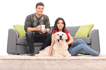 Young couple sitting with a dog on a modern sofa
