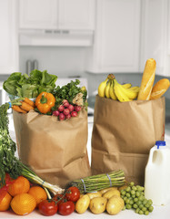 Assorted fruits and vegetables in brown grocery bag