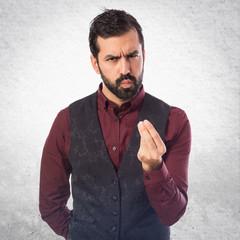 Man wearing waistcoat doing a money gesture