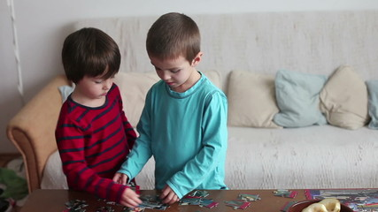 Smart little boys, brothers, making puzzle at home