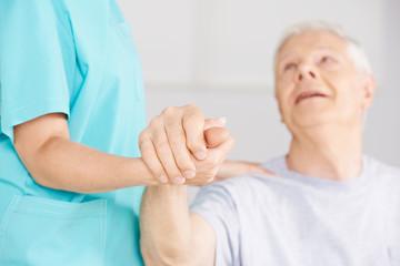 Krankenpflegerin hält Hand eines Senioren