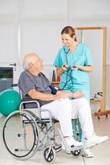 Blutdruck messen bei Senior im Rollstuhl