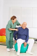 Senior mit schmerzendem Rücken bei Krankengymnastik