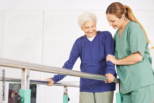 Leinwanddruck Bild Physiotherapeutin hilft Seniorin auf Laufband