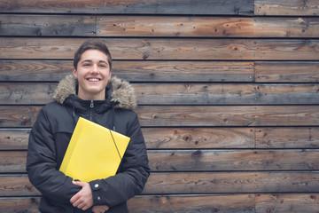 Schüler mit gelber Mappe lachend vor Holzwand