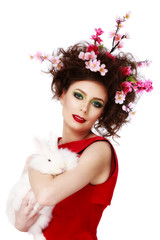 woman with a bunny, eggs and flowers spring easter concept