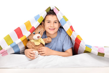 Playful kid holding a teddy bear under a blanket