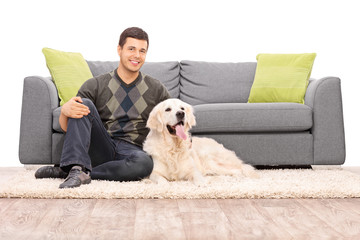 Young man sitting on the floor with his dog