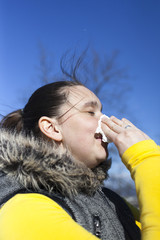 Pretty girl sneezing outdoors, on sunny windy day