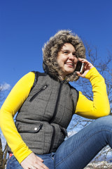 Pretty smilling young woman using smart cellphone outdoors