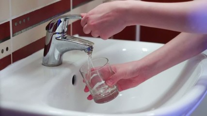 Man collects the water in a glass of tap water. Slow motion