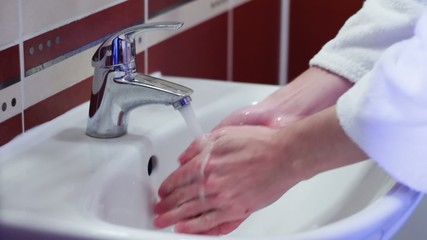 Man washes his hands in the sink