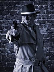 Gangster pointing a gun, wearing raincoat