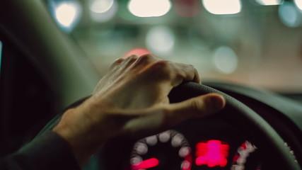 Hands of a man driving a car. Close up