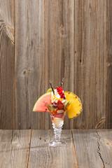 Früchte-Eisbecher auf Holzhintergrund