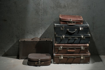 Obsolete suitcases are on each other on the floor
