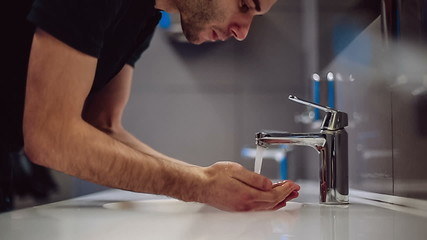 A man washes his hands and face. Slow motion