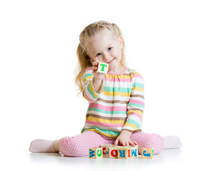child plays with building blocks and learning of letters