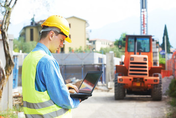 builder engineer with laptop at construction site