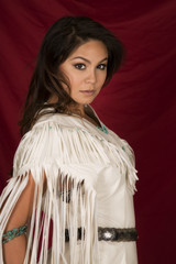 Native American woman in white on red side looking